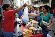 A woman buys goods at a popular street market in Caracas