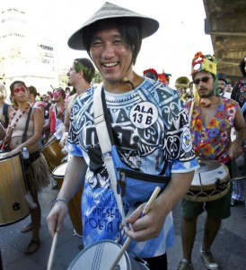 A Chinese tourist plays the drum along Rio Branco avenue, in downtown Rio de Janeiro, Brazil, during a parade of the Cordao do Boitata carnival street band