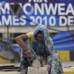 An Indian woman works in front of a torn Commonwealth Games banner in New Delhi on September 23, 2010