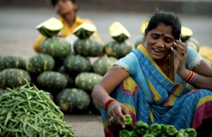 An Indian vegatable seller arranges vegatables as she speaks on a cellular phone at a roadside vegatable market in Allahabad