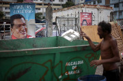 A man throws garbage next to a poster of Venezuelan President Hugo Chavez for the upcoming parliamentary elections, on September 21, 2010 at the low-income 23 de enero neighborhood, in Caracas