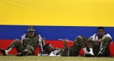 Colombian soldiers rest before a military ceremony