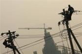 Workers fix wires on a wire pole along a road on March 31, 2006 in Beijing, China.