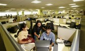 Software developers gather at a computer terminal at IBM in Bangalore, India on Friday, May 19, 2006
