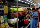 Indian employees polish fruit before placing it on shelves as they prepare the Reliance Fresh Store Outlet in Hyderabad, 02 November 2006.