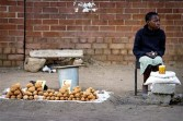  A young girl sells potatoes from a stall by the roadside, using the South African Rand and U.S. dollar in Harare, Zimbabwe, on Thursday, April 23, 2009.