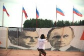 A youth takes a photo of a banner featuring portraits Russian President Dmitry Medvedev (L) and Prime Minister Vladimir Putin on July 4, 2011