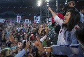 Yingluck Shinawatra raises her arm with a trademark salute, showing the sign of her party being first on the ballot sheet, to a large crowd of supporters