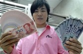 Chinese singer Hu Yenpin displays banknotes of Taiwanese and Chinese currency at a bank in Taipei on June 30, 2008.