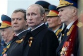 Russian President Dmitry Medvedev (L), Prime Minister Vladimir Putin (2nd L) and WW II veterans watch a military parade during the nation's Victory Day celebrations in Moscow on May 9, 2011