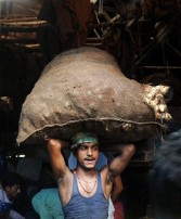An Indian labourer carries a sack of vegetables on his head at a wholesale market in Kolkata on September 14, 2011