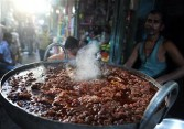 An Indian street vendor prepares a traditional dish at a roadside shop