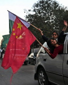 Pakistani children wave Pakistani and Chinese flags
