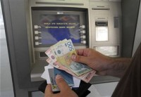 Serbian customer takes money from an ATM in Belgrade