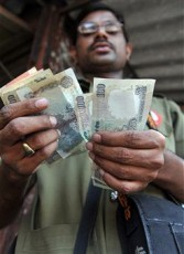 An Indian  bus conductor counts his rupees