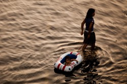 A woman pulls her daughter behind her in a small raft as she walks along a flooded street, near to the overflowing Chao Phraya river on November 1, 2011 in Bangkok, Thailand.