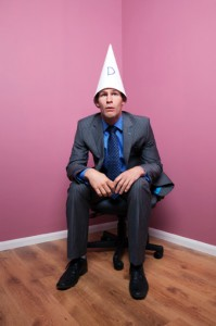 a man in a business suit with dunce cap