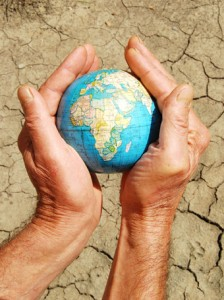 Hand cradles a globe above the cracked earth