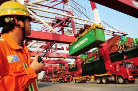 This photo taken on October 17, 2011 shows a worker monitoring the loading of containers on to a ship at the harbour in Qingdao, in northeast China's Shandong province (STR/AFP/Getty Images)