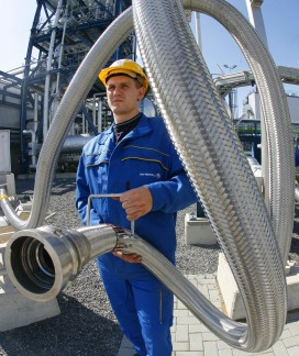 An employee poses with a pipe used to ca