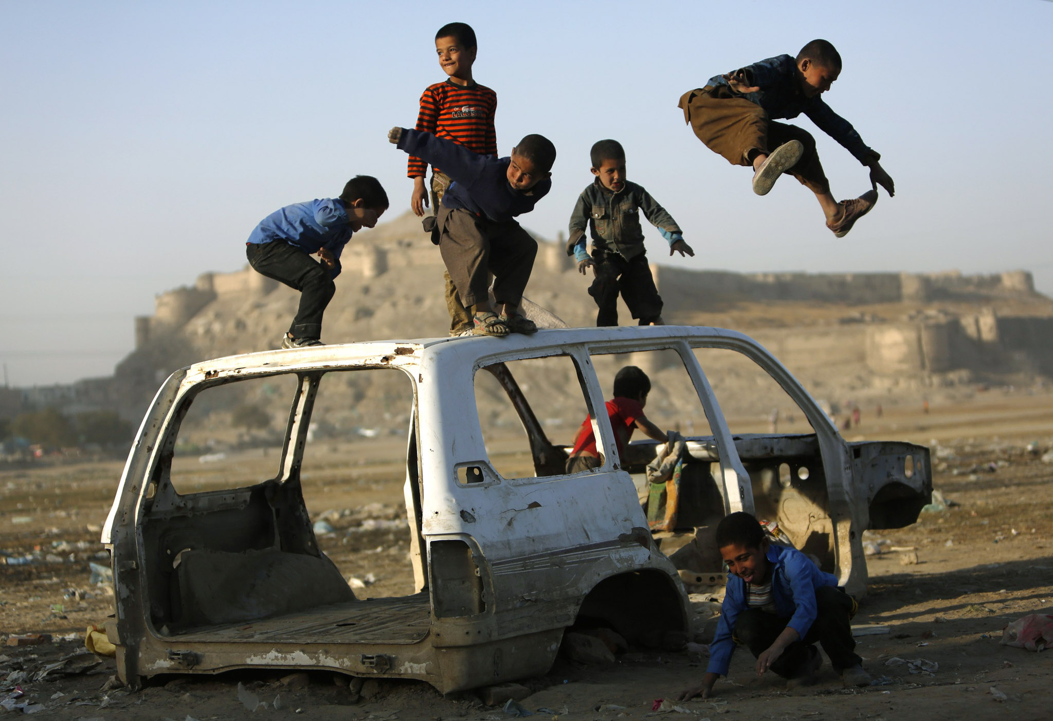 Afghan boys play on a destroyed car in Kabul...Afghan boys play on a destroyed car in Kabul October 22, 2013.  REUTERS/Mohammad Ismail