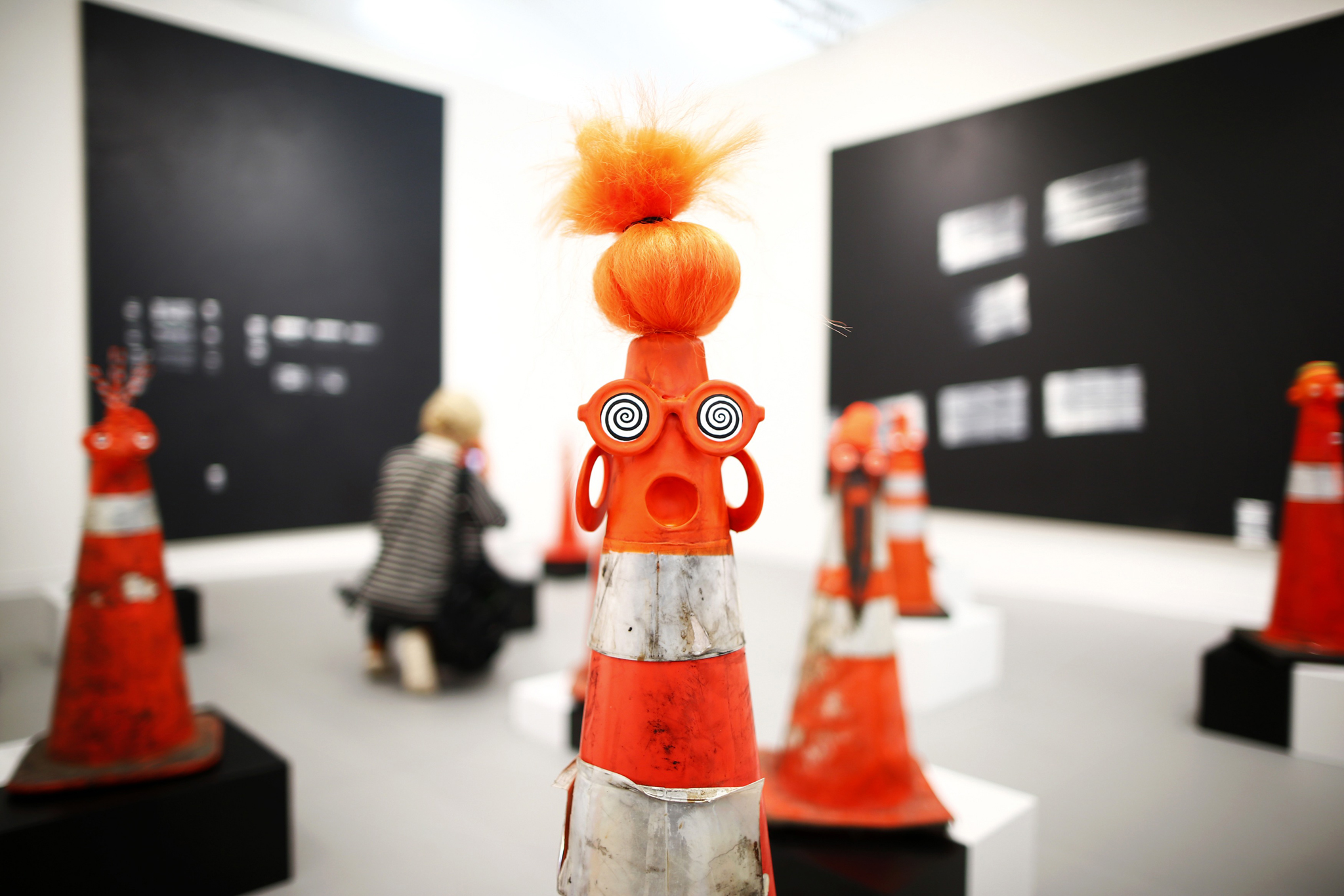 """A visitor photographs part of Robert Pruitt's """"Safety Cones"""" at the Frieze Art Fair in central London...A visitor photographs part of Robert Pruitt's """"Safety Cones"""" at the Gavin Brown's Enterprise from New York's stand at the Frieze Art Fair in central London, October 16, 2013. REUTERS/Andrew Winning"""