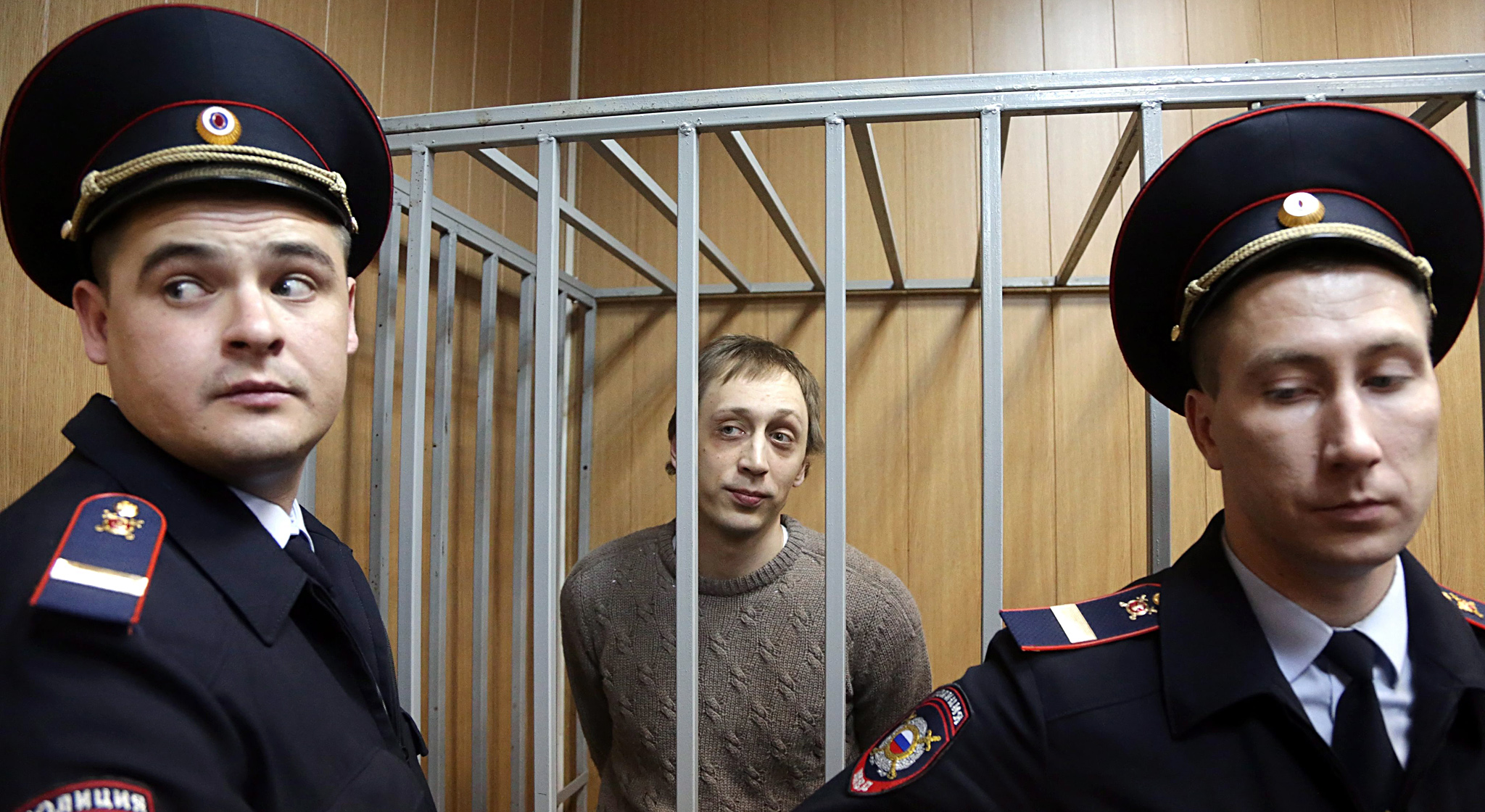 Pavel Dmitrichenko trial continues...epa03919128 Bolshoi Ballet dancer Pavel Dmitrichenko (C) is seen in the defendant's cage during a court hearing in Moscow, Russia, 22 October 2013. Dmitrichenko and two other men are accused of carrying out an attack on the famous troupe's master Sergei Filin on 17 January 2013.  EPA/MAXIM SHIPENKOV