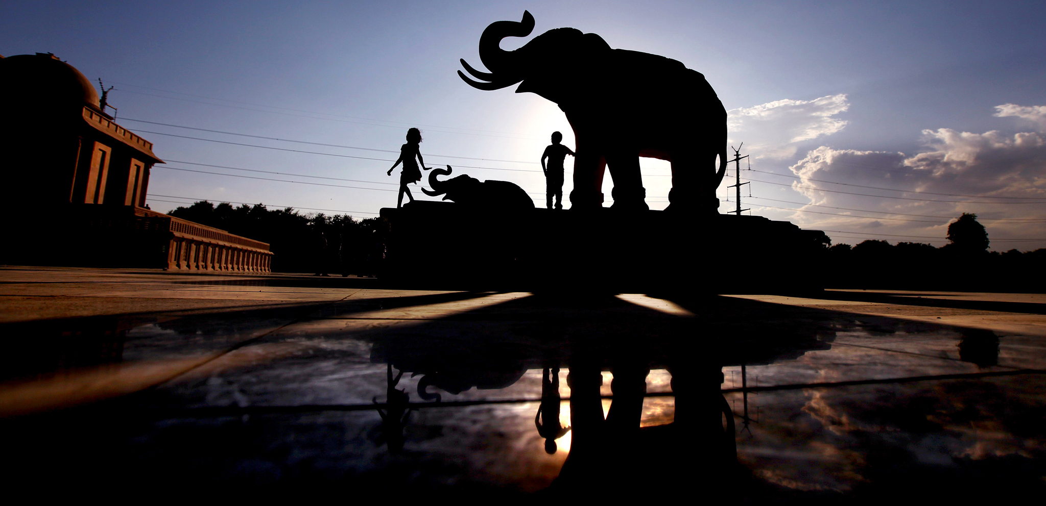 Indian children play next to an elephant statue at Ambedkar Park, dedicated to dalits or Indiaís low-castes, which was opened to the public Wednesday, in Noida, on the outskirts of New Delhi, India, Wednesday, Oct. 2, 2013. The park was built during the rule of the Bahujan Samaj Party (BSP) government and includes statues of elephants, the political symbol of the BSP, as well as statues of dalit leaders. It was opened despite an investigation by the current government into millions it says were misappropriated during the building of the park.  (AP Photo/Altaf Qadri)