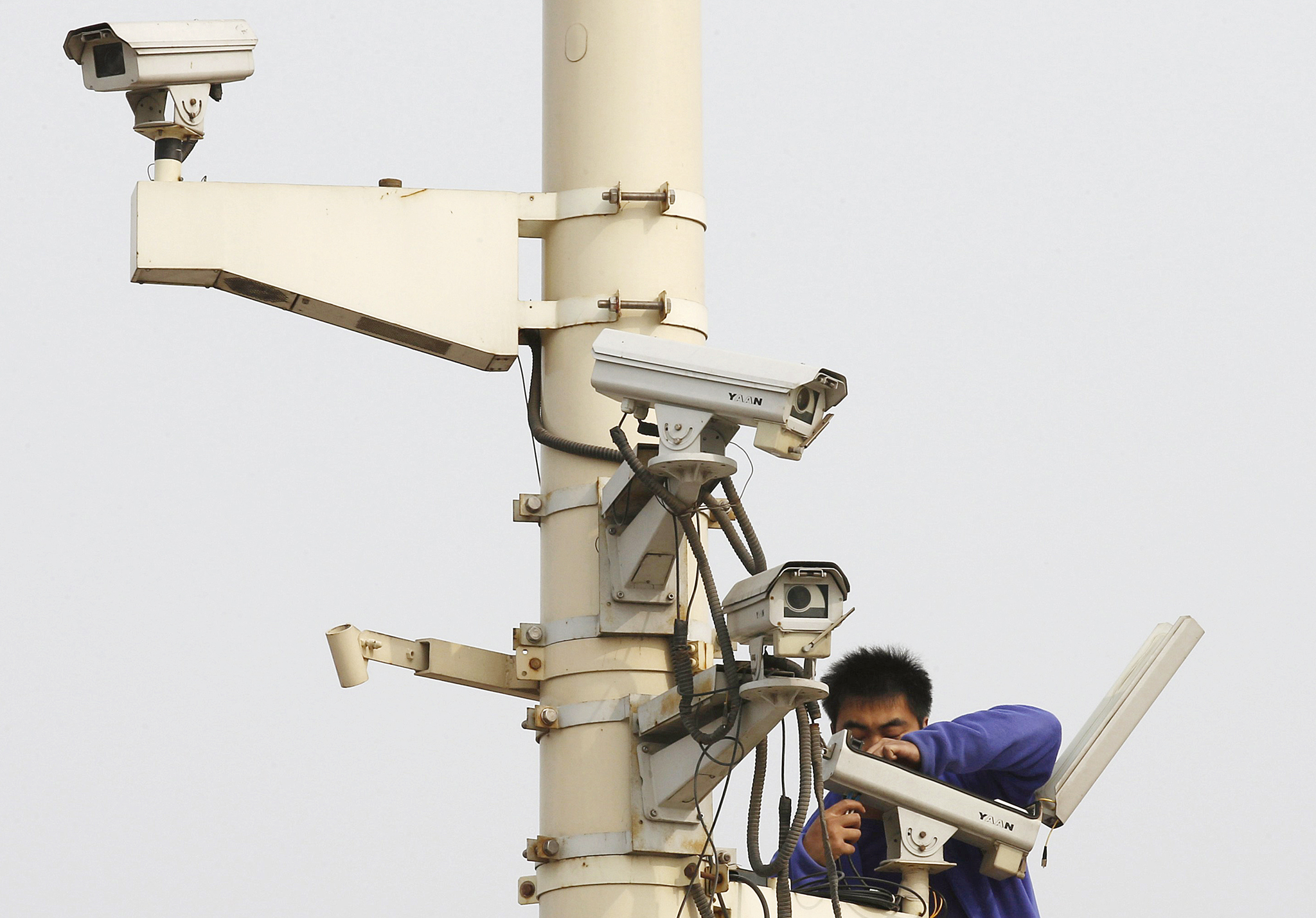 REUTERS PICTURE HIGHLIGHT...ATTENTION EDITORS - REUTERS PIC    PEK703  A man works on a security camera which is installed at Tiananmen Square in Beijing.  REUTERS/Kim Kyung-Hoon