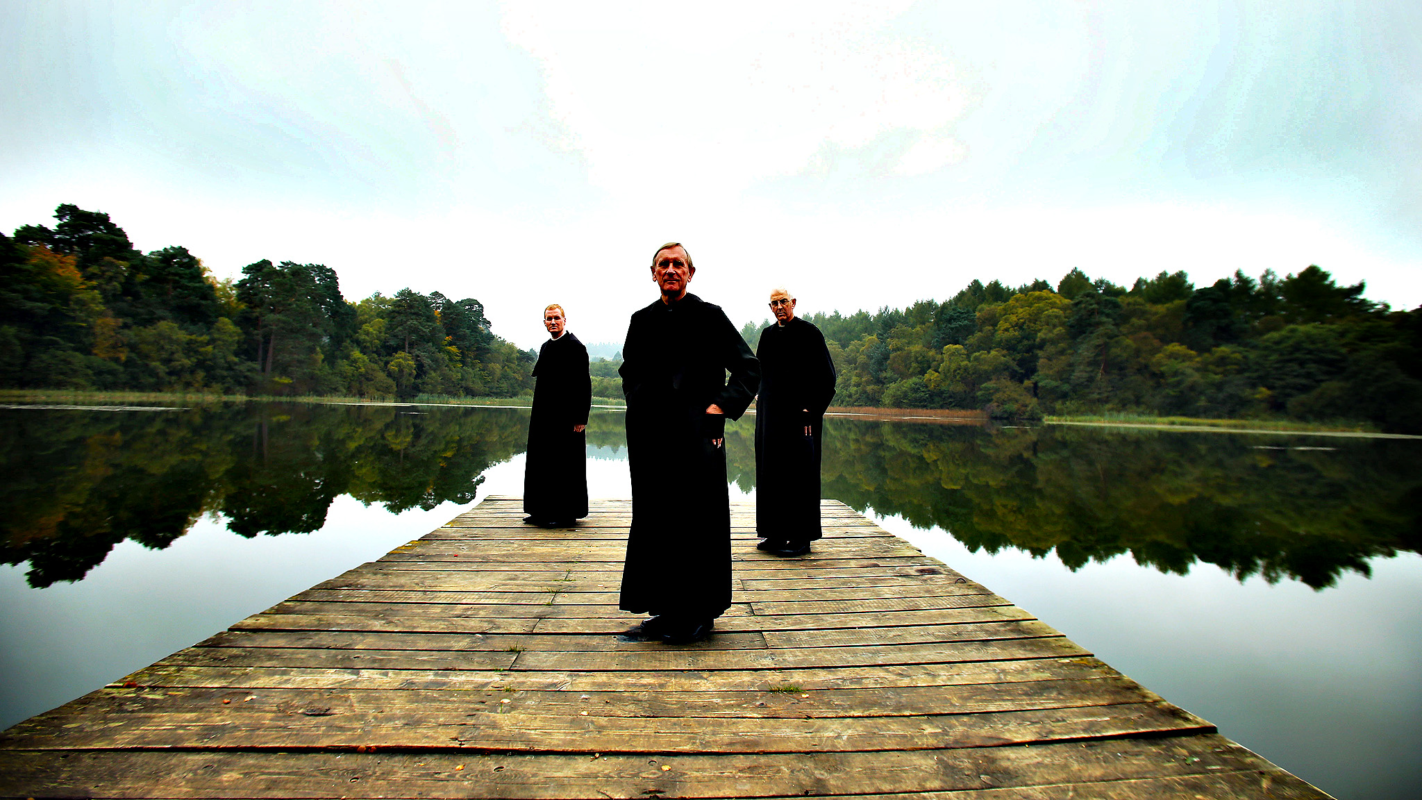(left to right) Father Luke and Father Gordon and Father Matthew look out over the lake at Ampleforth, North Yorkshire  at the Autumn trees. Ampleforth Abbey and College is the UK's largest Benedictine community and is set in one of North Yorkshire's Areas of Outstanding Beauty.