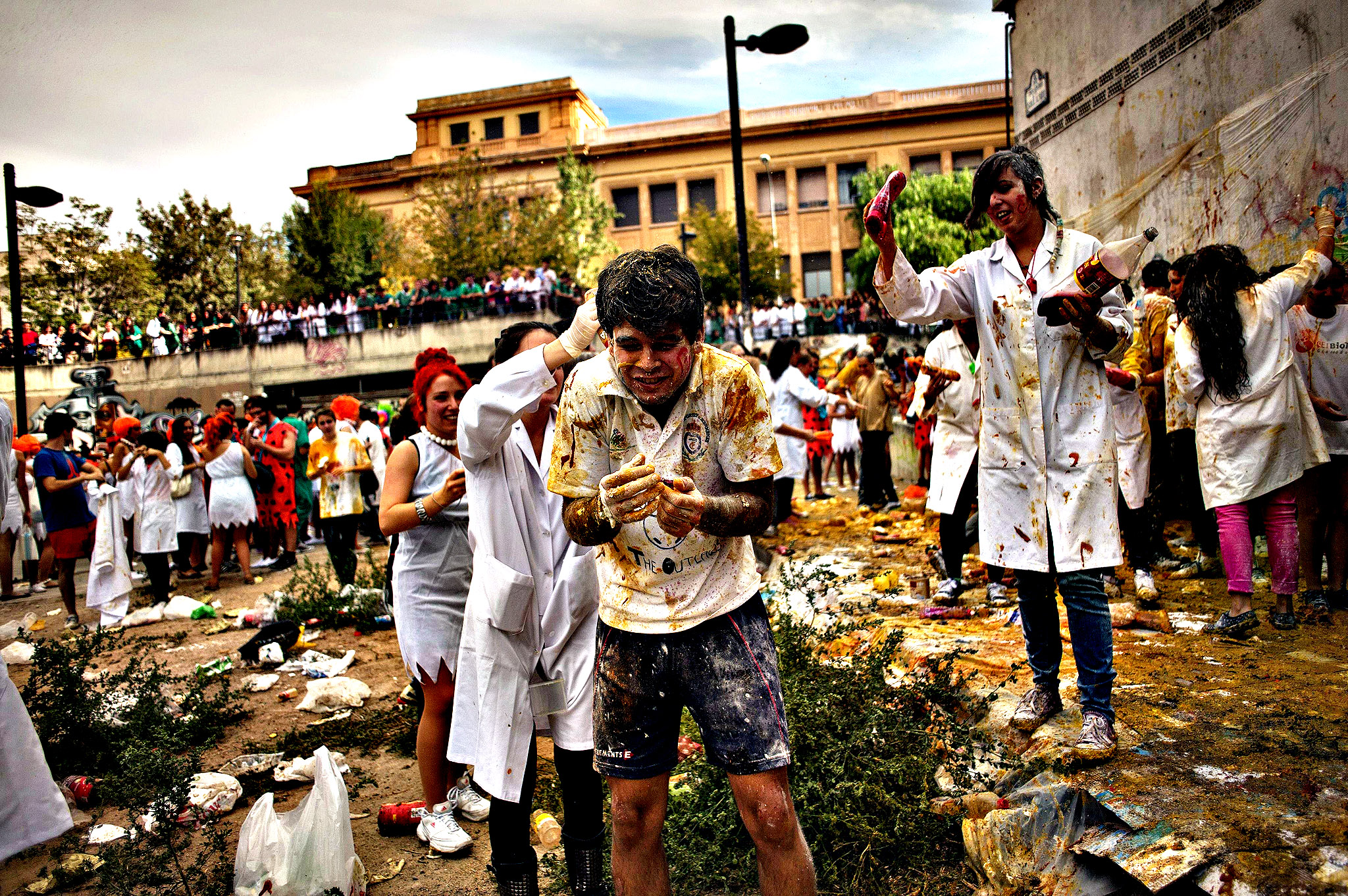 Medical students pour tomato sauce on a fresher of the Faculty of Medicine during a hazing at the University of Granada, in Granada
