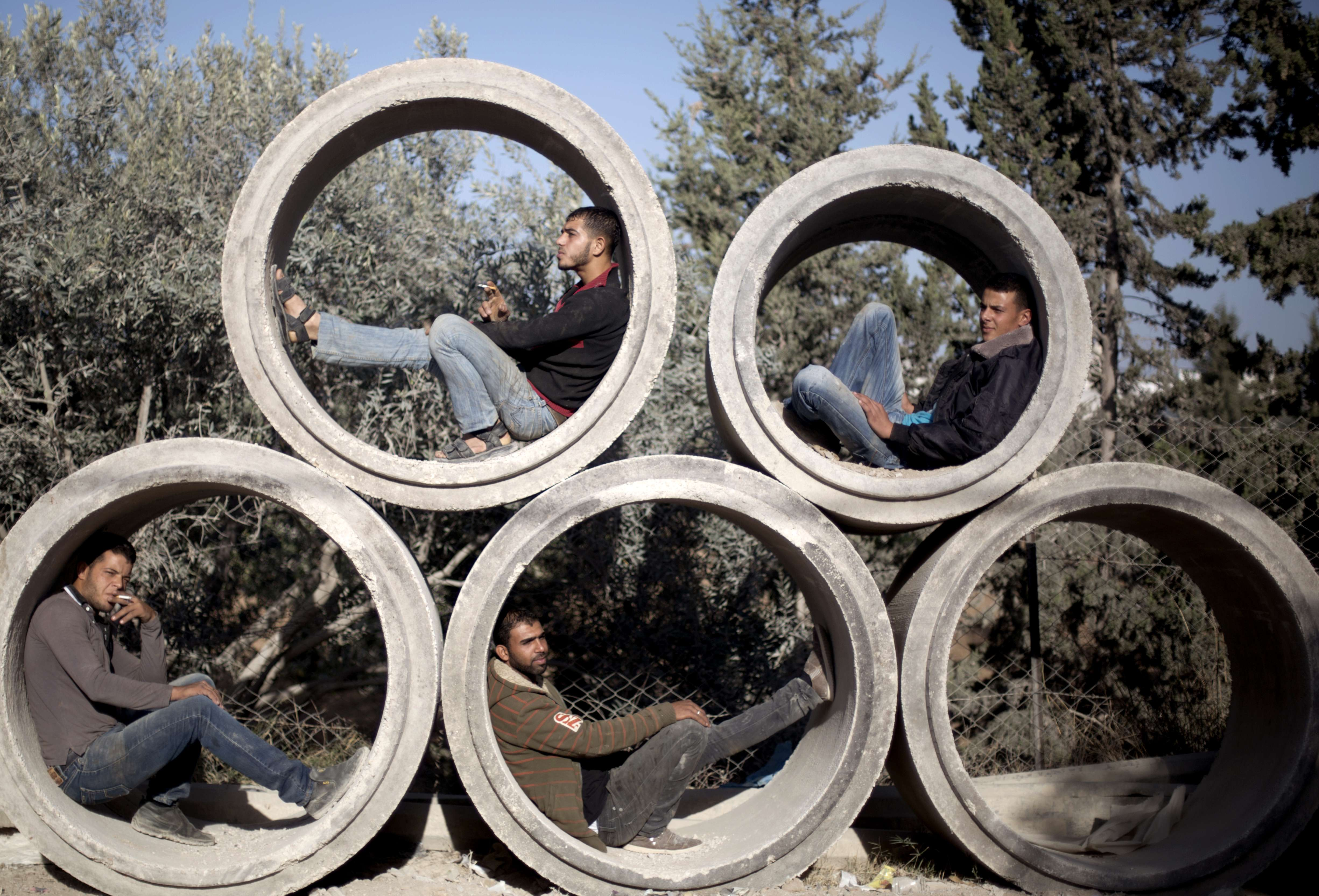 Palestinian factory workers rest inside ...Palestinian factory workers rest inside concrete pipes as they wait for the start of a working day in Gaza City on October 23, 2013. AFP PHOTO/MOHAMMED ABEDMOHAMMED ABED/AFP/Getty Images