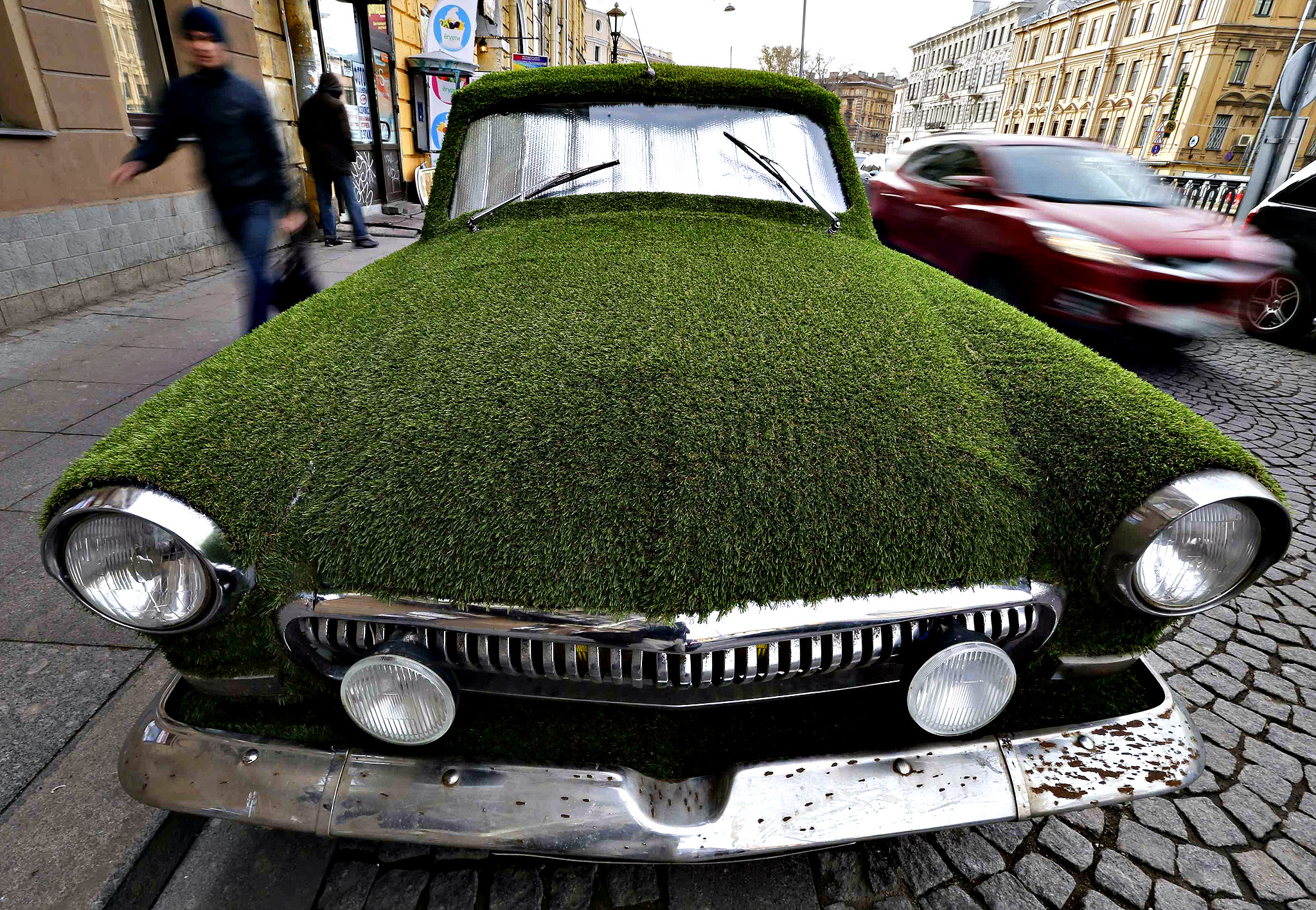 A customized Soviet-era Volga GAZ-21 vintage car covered by artificial grass, advertising for a dairy store, is seen on a parking lot in St. Petersburg, October 17, 2013.