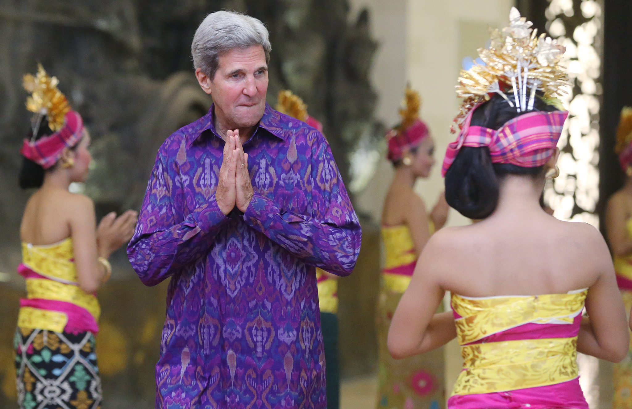 APEC 2013 summit in Indonesia...epa03900660 US Secretary of State John Kerry, welcomed by Indonesian beauties, gestures while arriving with Russian President Vladimir Putin (L) for a group photo at Asia-Pacific Economic Cooperation (APEC) Summit  in Nusa Dua , Bali, Indonesia, 07 October 2013  EPA/SERGEI CHIRIKOV