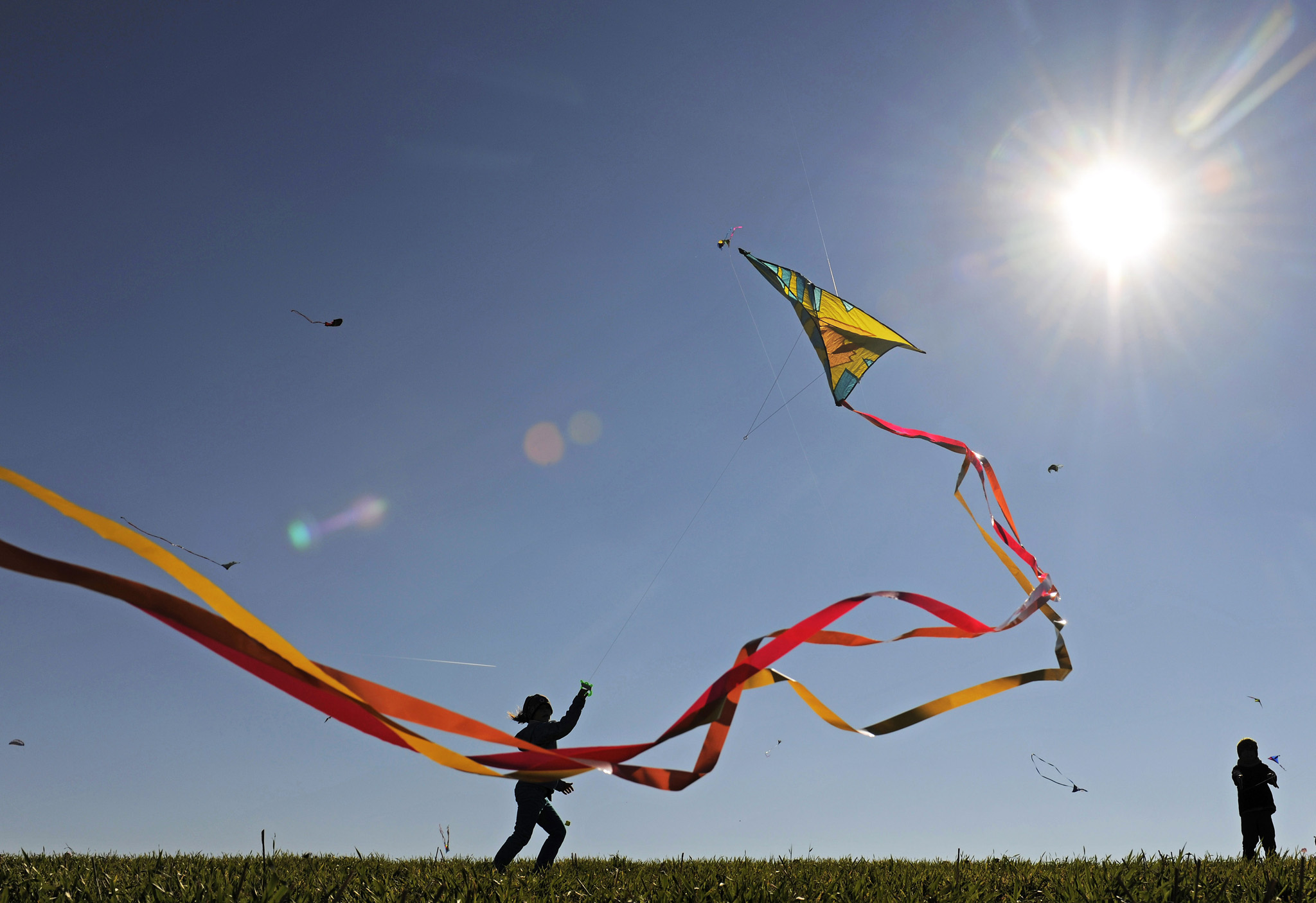 A child runs with its kite during bright sunshine near Chemnitz, eastern Germany, Thursday, Oct. 3, 2013. Meteorologists predict changeable weather for the upcoming days in Germany.