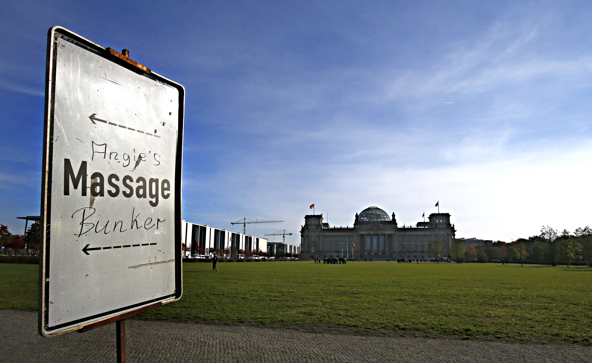 "A road sign with graffiti reading ""Angie's Massage Bunker"" is pictured at the square in front of the Reichstag building"