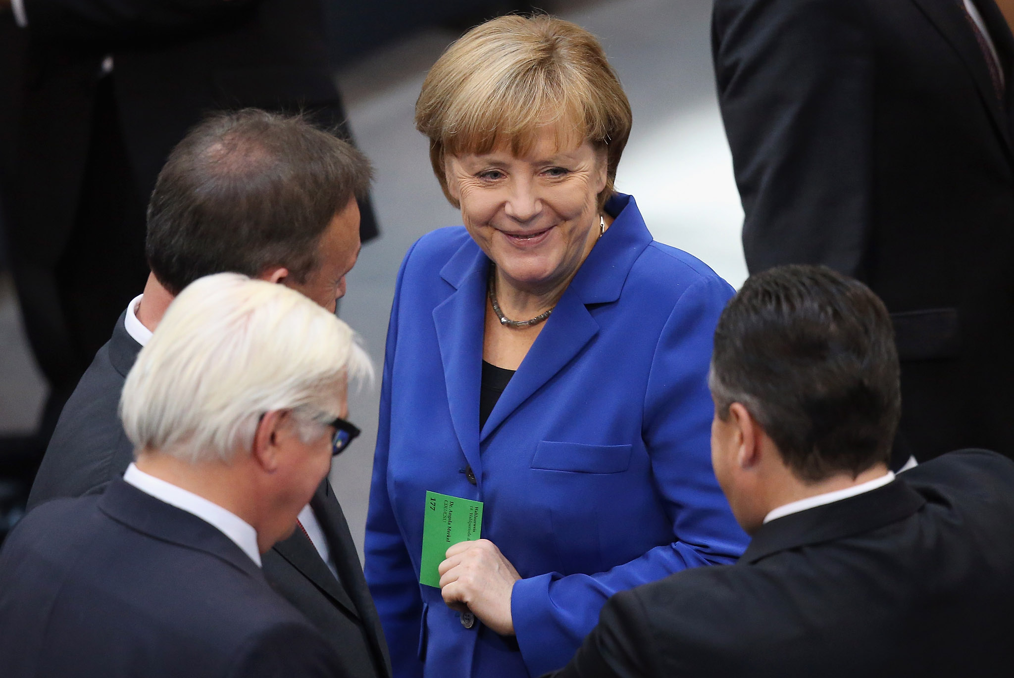 New Bundestag Convenes As Old Government Is Dismissed...BERLIN, GERMANY - OCTOBER 22:  German Chancellor and Chairwoman of the German Christian Democrats (CDU) Angela Merkel (C) chats with leading German Social Democrats (SPD) members Sigmar Gabriel (R), Thomas Oppermann (L) and Frank-Walter Steinmeier at the first session of the new Bundestag following recent nationwide  elections on October 22, 2013 in Berlin, Germany. The session heralds the beginning of the 18th legislative period, though the German government remains in transition as the Christian Democrats (CDU) and German Social Democrats (SPD) are still in the process of coalition negotiations whose outcome remains u