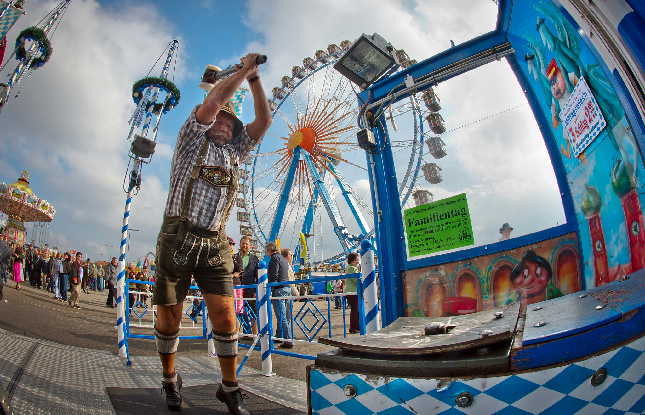 "Oktoberfest 2013...MUNICH, GERMANY - OCTOBER 1:  A bavarian visitor in a traditional ""Lederhosen""  participates in a  funfair attraction called ""Hau den Lukas"" at the Oktoberfest 2013 beer festival at Theresienwiese on October 1, 2013 in Munich, Germany. At the funfair attraction ""Hau den Lukas"" you have three tries to hit the target with a hammer so hard that a bell at the top rings. The Munich Oktoberfest, which this year will run from September 21 through October 6, is the world's largest beer fest and draws millions of visitors. (Photo by Joerg Koch/Getty Images)"