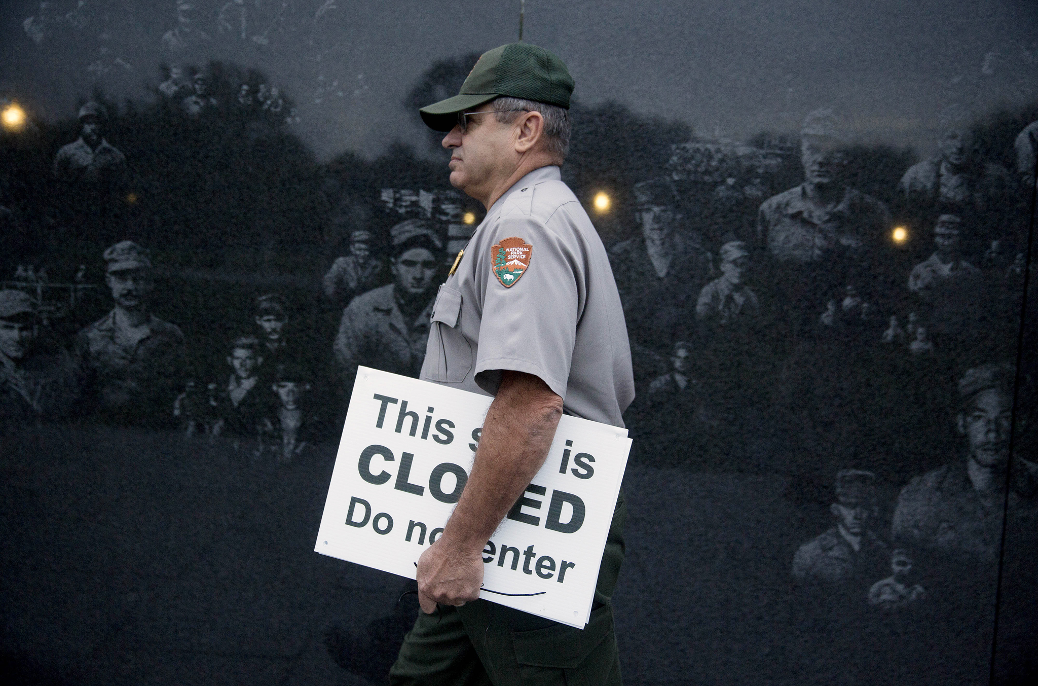 Congress Vote Ends Impasse to Be Revisited in January...National Park Service park ranger Richard Trott walks through the Korean War Veterans Memorial with a closed sign he removed in Washington, D.C., U.S., on Thursday, Oct. 17, 2013. After the partisan passions and heated rhetoric, the disruptions of a government shutdown and displays of dysfunction, Congress did what it could have done weeks ago: voted to fund the government and lift the debt limit. Photographer: Andrew Harrer/Bloomberg