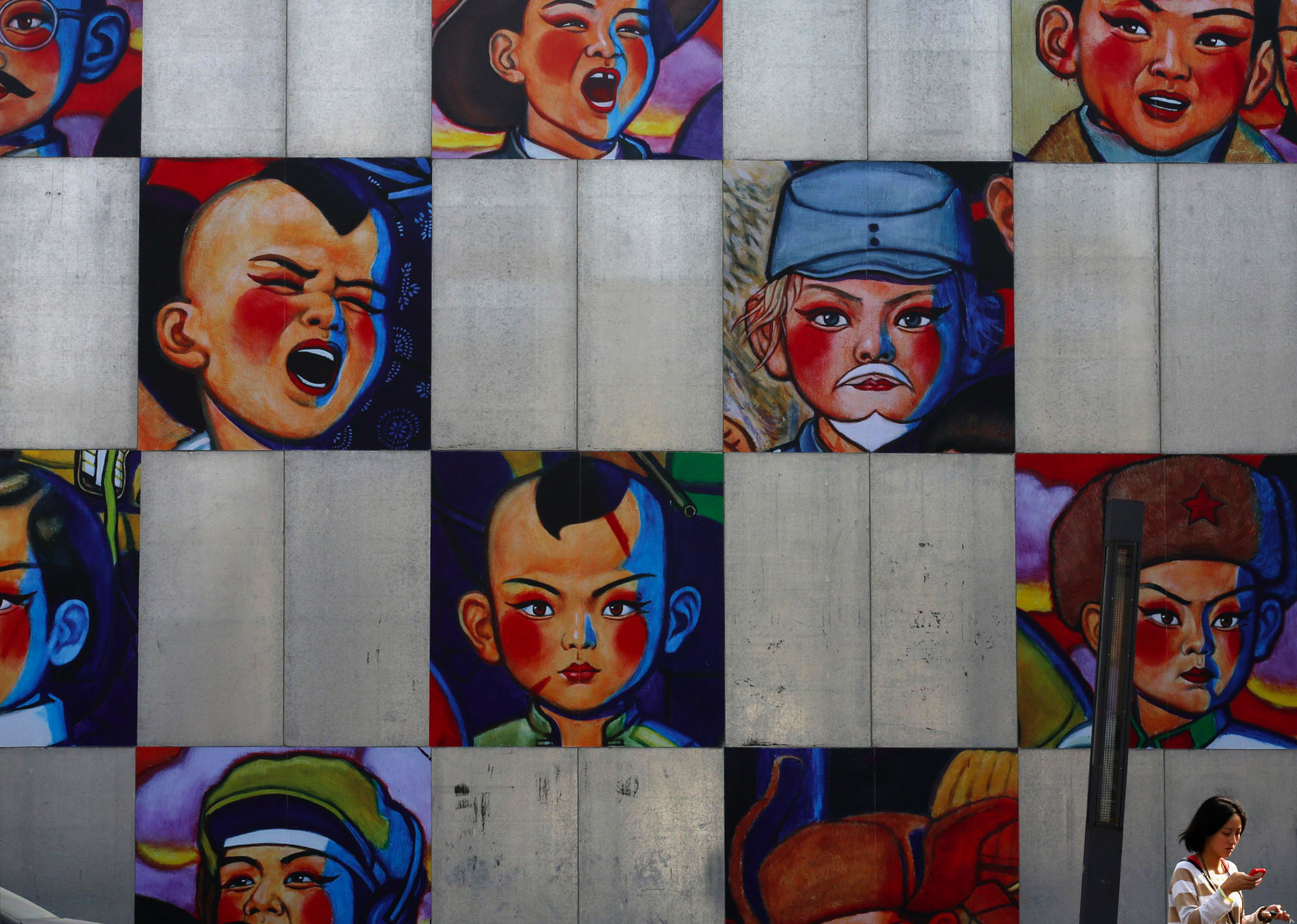 A woman walks past a gallery's wall bearing the paintings by Song Changqing during the 2013 Beijing 798 Art Festival at the 798 Art Zone in Beijing. The art zone, originally an unused factory, was transformed into a landmark of contemporary art in Beijing in the 1990s. The annual art festival goes on till the 20th October.