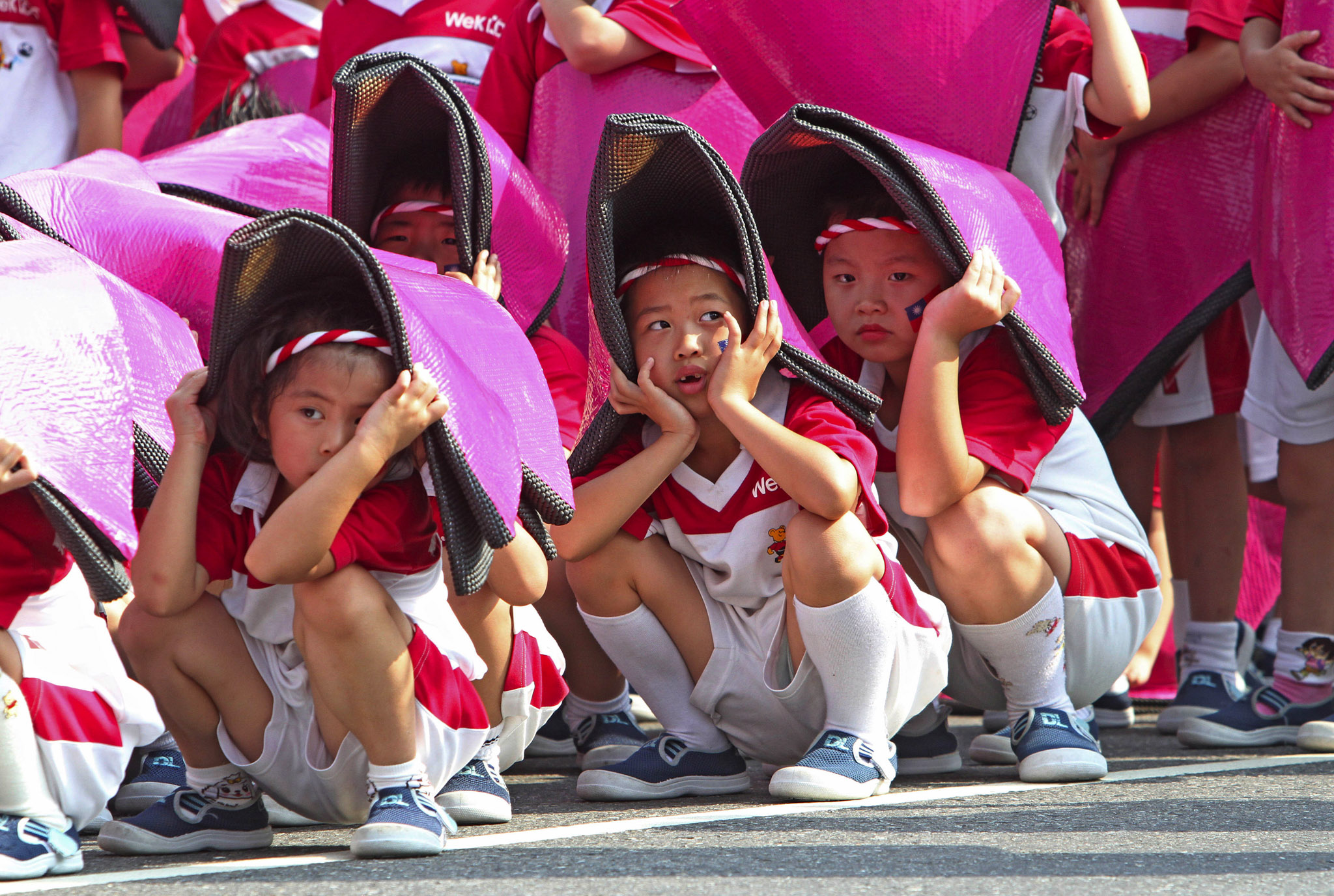 Taiwanese children cover their head to keep from Sun during a rehearsal for National Day celebrations in front of the Presidential Office in Taipei, Taiwan. National Day is known as Double-Ten, because it falls on October 10, the tenth day of the tenth month of the year. It commemorates the Republican Revolution, which broke out in Wuhan, China, on the 10th October 10, 1911, and brought about the end of China's Qing dynasty.