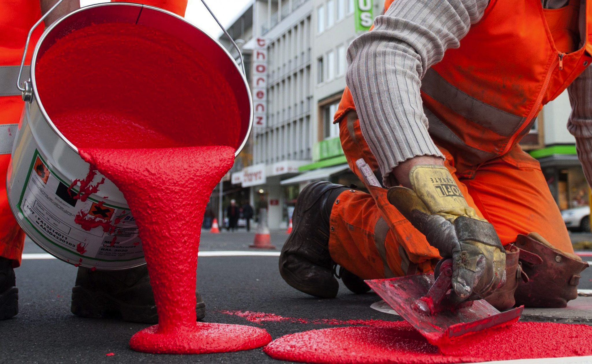 A construction worker applies red paint to mark cycle lanes in Hanover, Germany.