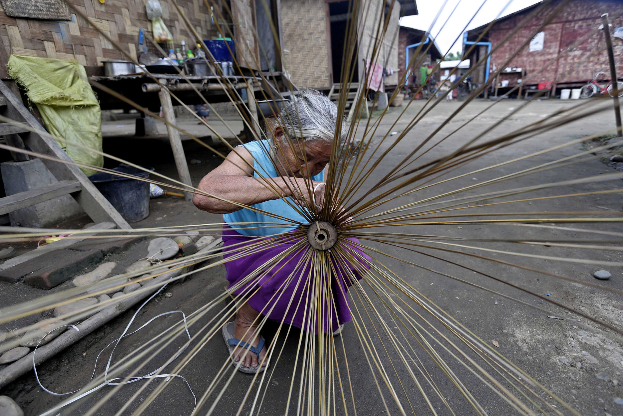 An elderly Kachin refugee woman maiking a broom at the Janmai Baptist camp, Myitkyina, Kachin State. Thousands of local people left their homes and took shelter in refugee camps to escape the ongoing battles between the Myanmar government's troops and the Kachin Independence Army (KIA).
