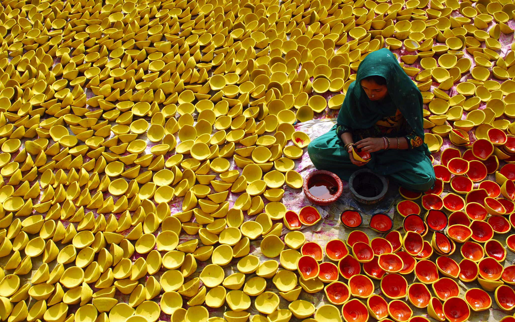 An Indian potter paints earthenware lamps ahead of Diwali, or the Hindu festival of lights, in Amritsar, India. Hindus light lamps, wear new clothes, exchange sweets and gifts and pray to goddess Lakshmi during the festival.
