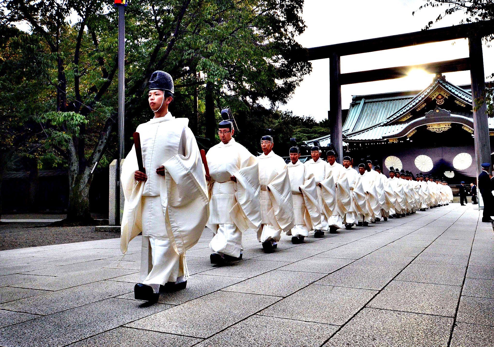 "Shinto priests walk out from Torii gate after they administer a Shinto rite ""Kiyoharai"" on the first day of the four-day autumn festival at the Yasukuni shrine in Tokyo on October 17, 2013. Japanese Prime Minister Shinzo Abe has donated a symbolic gift to the controversial Yasukuni war shrine, an apparent sign that he will avoid a visit that would have angered China and South Korea."