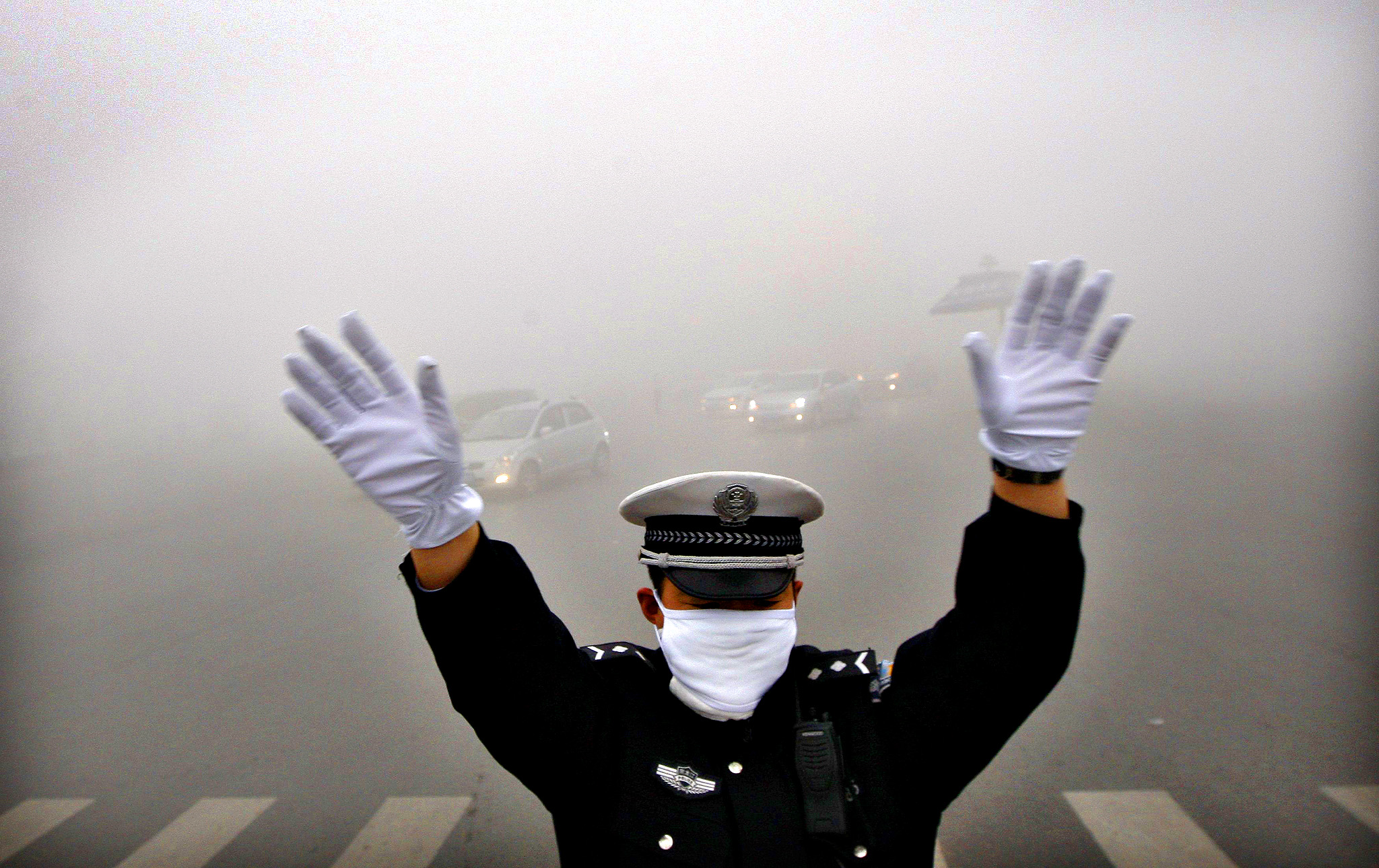 A traffic policeman signals to drivers during a smoggy day in Harbin, Heilongjiang province, October 21, 2013. The second day of heavy smog with a PM 2.5 index has forced the closure of schools and highways, exceeding 500 micrograms per cubic meter on Monday morning in downtown Harbin, according to Xinhua News Agency.