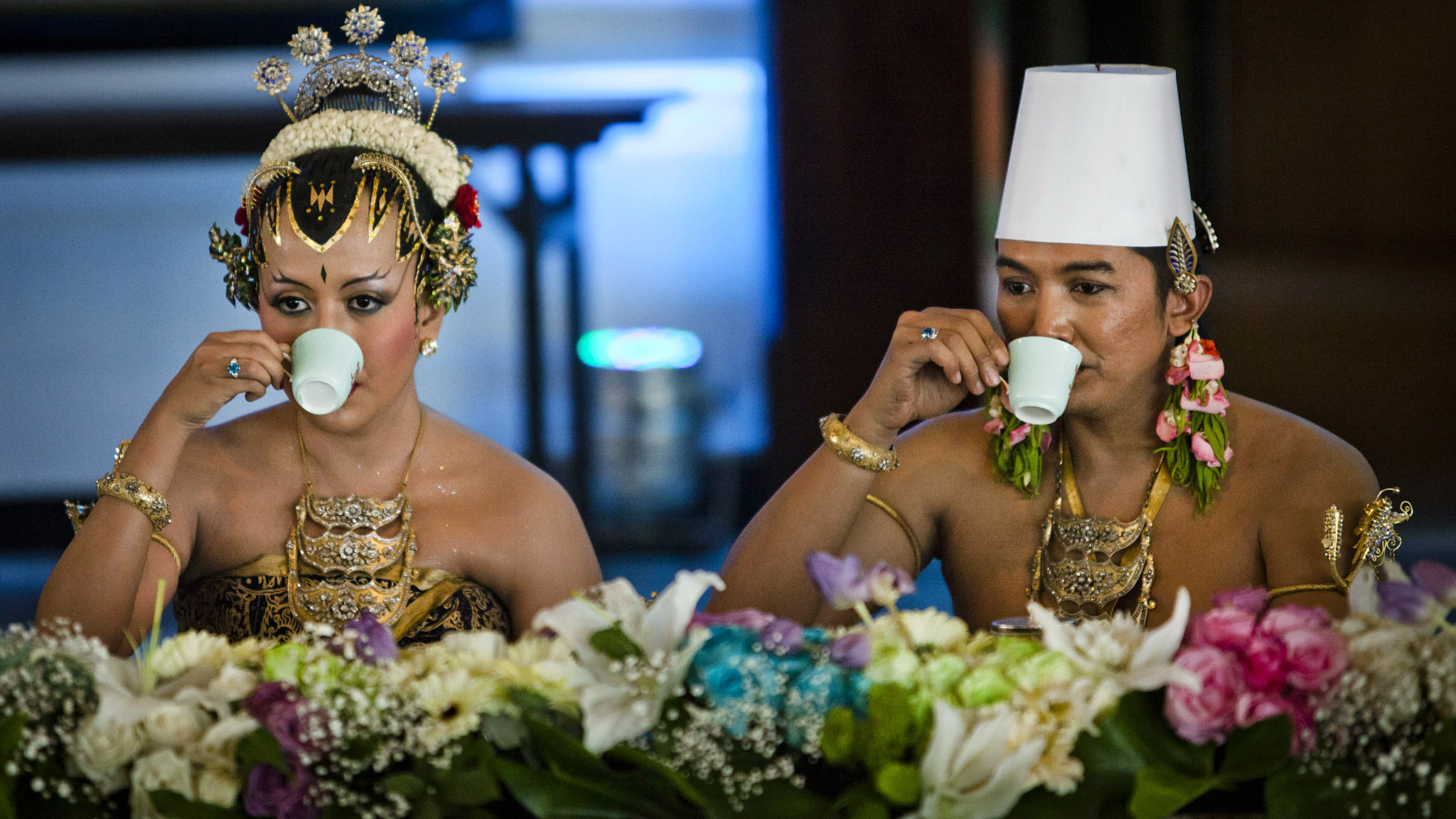 YOGYAKARTA, INDONESIA - OCTOBER 22:  KPH Notonegoro and Gusti Kanjeng Ratu Hayu drink tea during Dahar Klimah ceremony in Bangsal Kesatriyan at Kraton Palace as part of the Royal Wedding Held For Sultan Hamengkubuwono X's Daughter Gusti Ratu Kanjeng Hayu And KPH Notonegoro on October 22, 2013 in Yogyakarta, Indonesia.  Wedding celebrations will take place October 21-23 October. The wedding parade will include 12 royal horse drawn carriages and will be streamed live on the internet so that it can be watched by people all over the world.  (Photo by Ulet Ifansasti/Getty Images)
