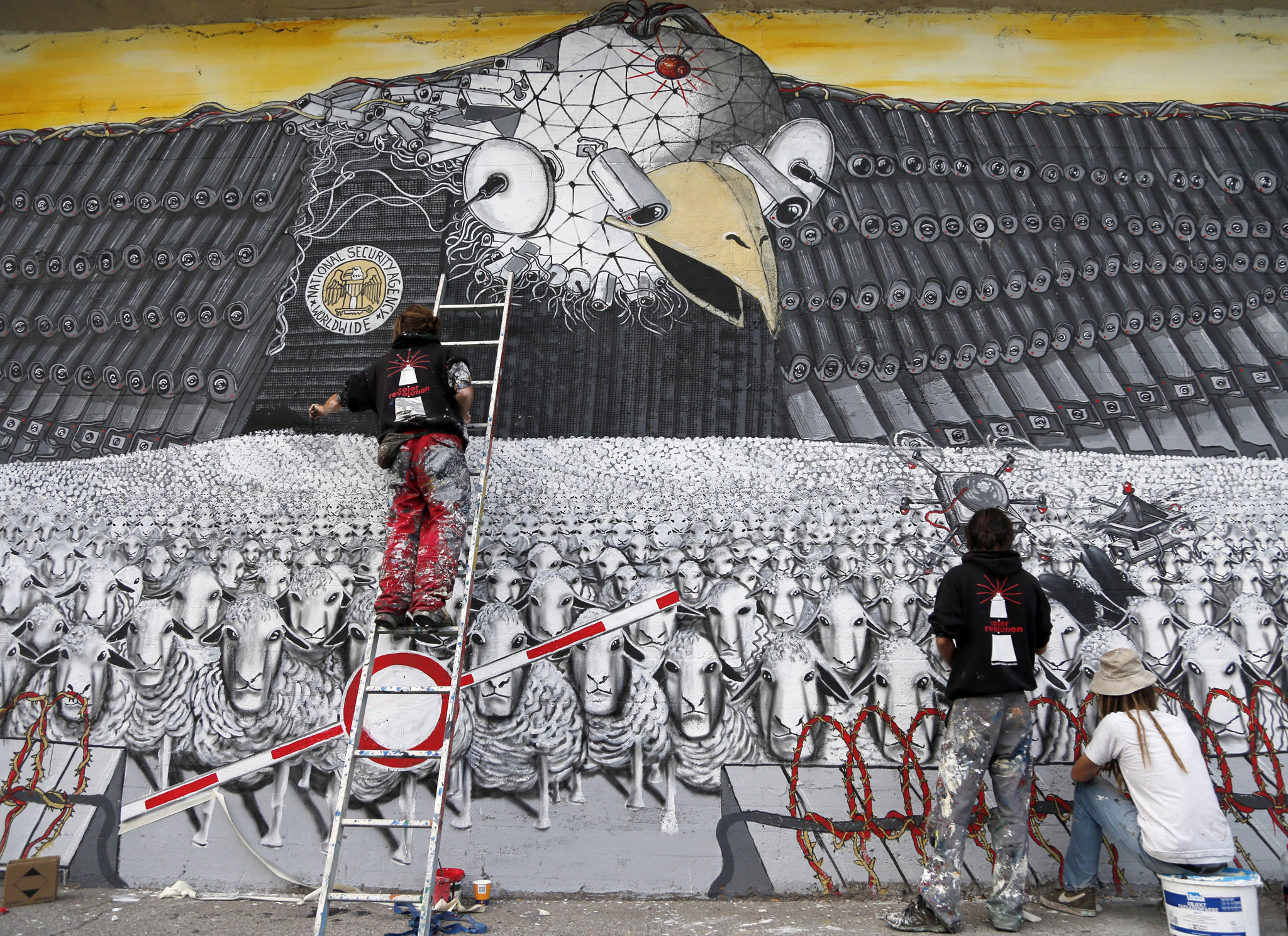 Artists A.Signl, left, and B.Shanti, second from right, of the artist group Captain Borderline paint their mural   'Surveillance of the fittest' at a wall in Cologne, Germany, Thursday, Oct. 24, 2013. The painting shows an American Bald Eagle with surveillance cameras watching a herd of sheep to draw attention to the spying program of the American National Security Agency. Germany demanded answers to ìall open questionsî about U.S. surveillance Thursday following allegations that American intelligence may have targeted Chancellor Angela Merkelís cellphone, and her chief of staff noted that Washington hasnít denied past snooping.