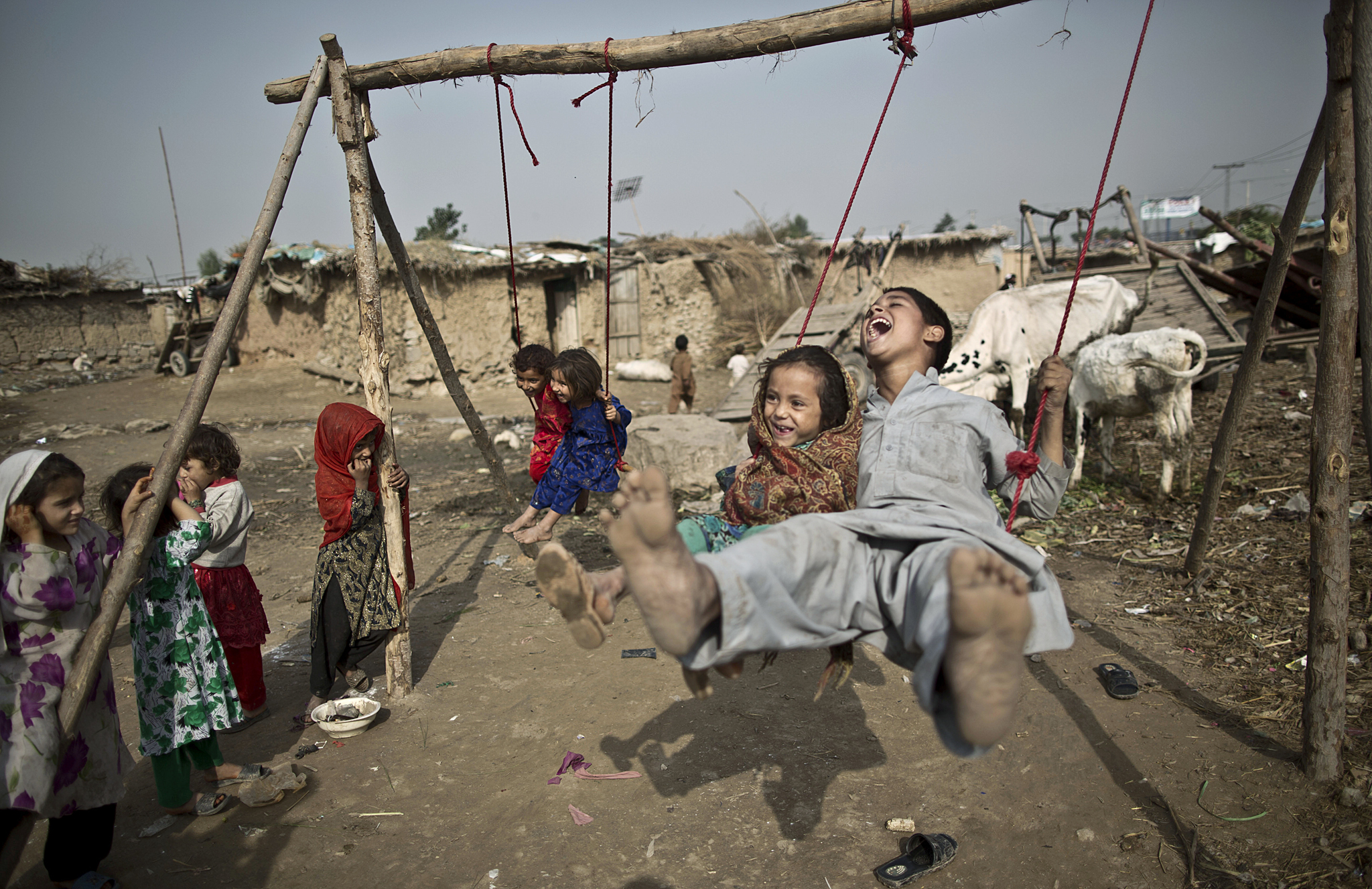 An Afghan refugee boy and his sister enjoy a ride on an improvised swing, in a poor neighborhood on the outskirts of Islamabad, Pakistan, Thursday, Oct. 31, 2013. Pakistan hosts over 1.6 million registered Afghans, the largest and most protracted refugee population in the world, according to the U.N. refugee agency, thousands of them still live without electricity, running water and other basic services.