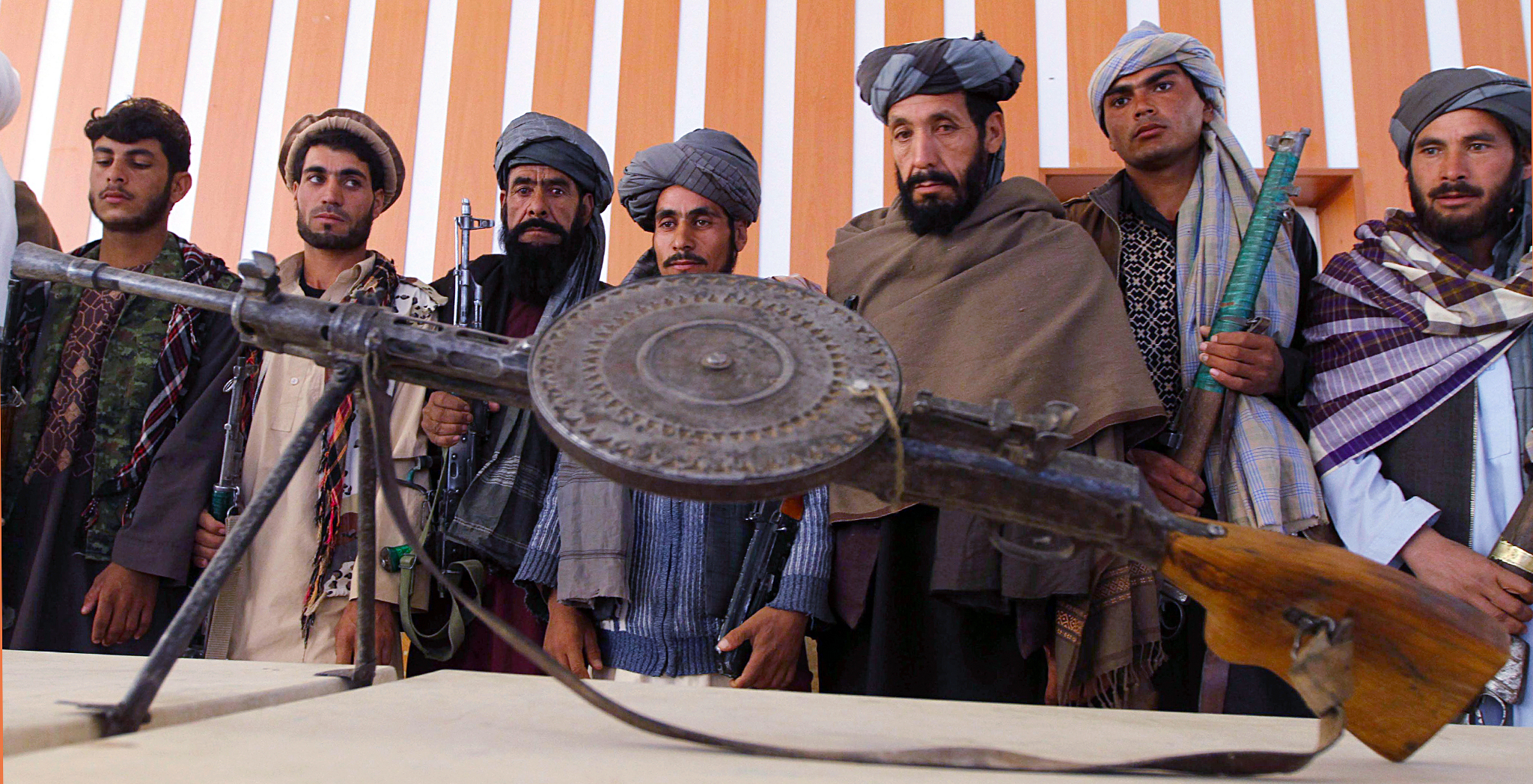 Taliban militants surrender their weapons in Herat...epa03920206 Former Taliban militants stand behind an rusty old light machine gun as they surrender their weapons under a US-backed Afghan government amnesty program, in Herat, Afghanistan, 23 October 2013. Hundreds of anti-government militants have so far surrendered to the government under an amnesty program launched by Afghan President Hamid Karzai back in 2004. Taliban-led militants have been waging a bloody war against Afghan and NATO forces for a decade, often infiltrating Afghan security forces and carrying out deadly attacks on NATO and Afghan forces.  EPA/JALIL REZAYEE